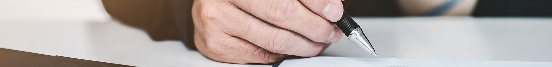 person signing a paper